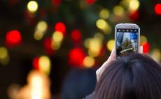 Jemand macht mit dem Smartphone ein Foto von einem Weihnachtsbaum